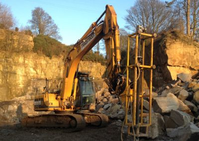 Excavator with pneumatic drilling rig preparing for controlled blasting of stone from quarry